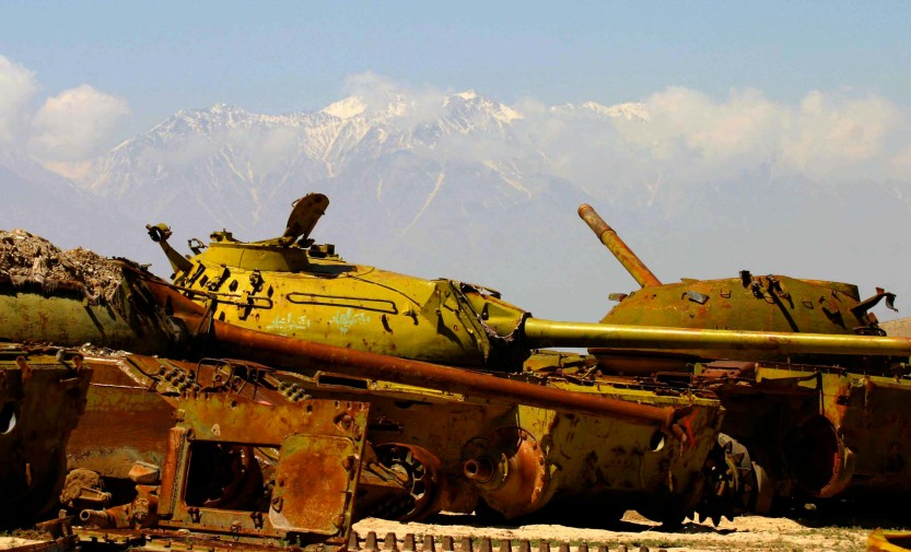 Graveyard of Russian tanks surrounded by snowy mountains, Afghanistan