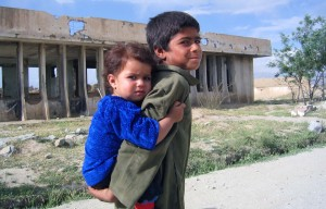 Boy and girl outside bombed out school, Afghanistan